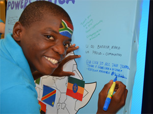 Samsung Youth Reporter, Refiloe Machaba, writing a message of support on the Samsung campaign board.