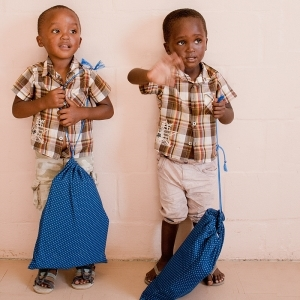 Twin boys receiving bags of stationery, March 2013.