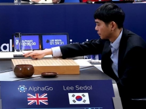 Go world champion Lee Sedol places the first piece against Google's artificial intelligence program AphaGo.