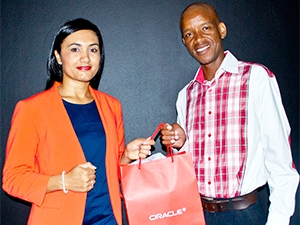 Leeya Hendricks, Marketing Director at Oracle, hands over the IaaS Survey prize to lucky prize winner Mmoni Thekiso.