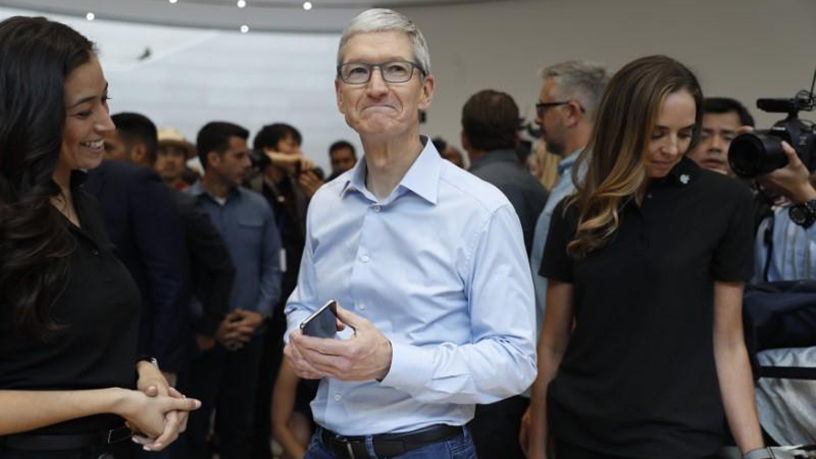 Apple CEO Tim Cook demonstrates a new iPhone after the presentation.